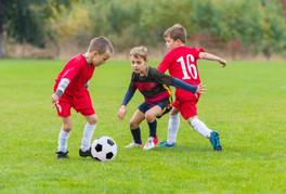 boys kicking football on the sports fiel