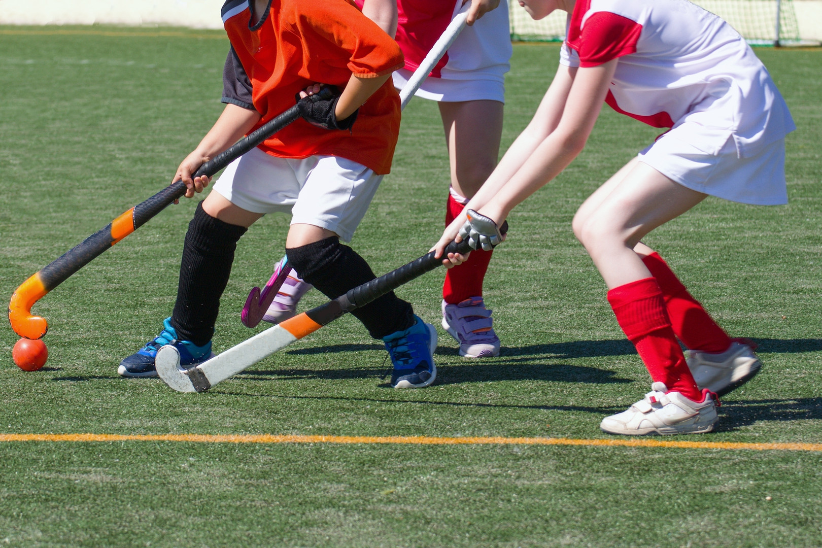 Children playing field hockey competitiv