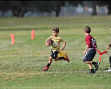 Young boy running with the ball during a