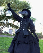 Person in all black dress and black plague doctor mask holding a spherical lantern