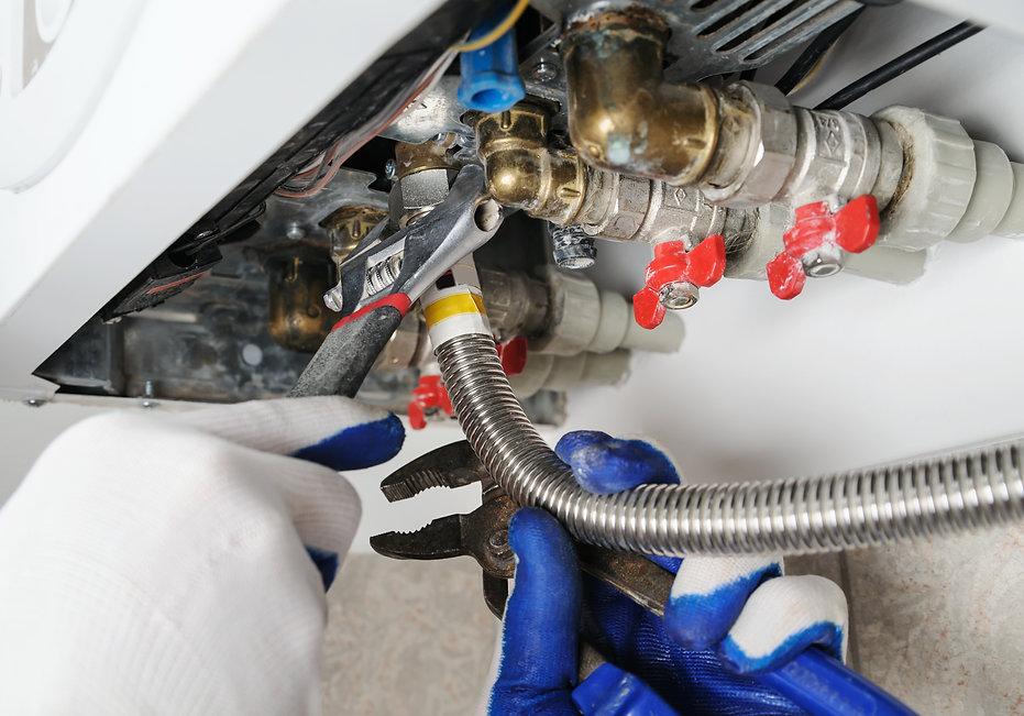 plumber-attaches-pipe-gas-boiler.jpg