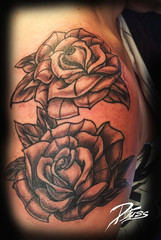 Tattoo of traditional neo roses on a woman's shoulder.