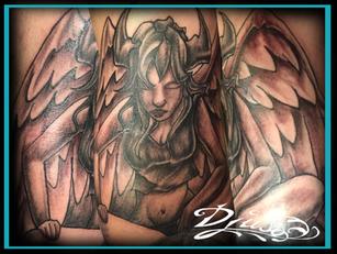 Tatouage d'un ange diabolique cornu en trai de méditer.