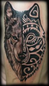 Tatouage d'une tête de loup polynésienne et semi réaliste sur le bras d'un homme