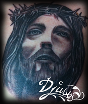Tattoo of a portrait of Jesus Christ in black and gray on the breastplate of a man.