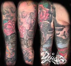 Tatouage d'une manche musicale avec crâne, guitare réaliste et micro old school. Tatouage sur le bras d'un homme.