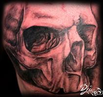 Tatouage d'un crâne réaliste sur le pectoral d'un homme.