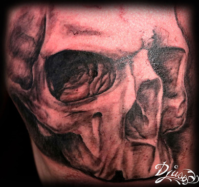 Tattoo of a realistic skull on the breastplate of a man.