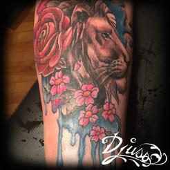 Tatouage d'un lion watercolour sur le bras d'une femme