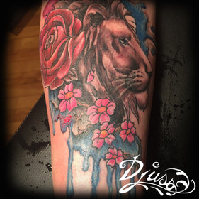 Tattoo of a watercolor lion on a woman's arm