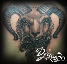 Tattoo of a psychic goat with worms in the mouth, tattoo on the back of a man.