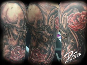Tattoo of a kiss of the dead. Muerta and skeleton kissing with a rose. tattoo on the arm of a man