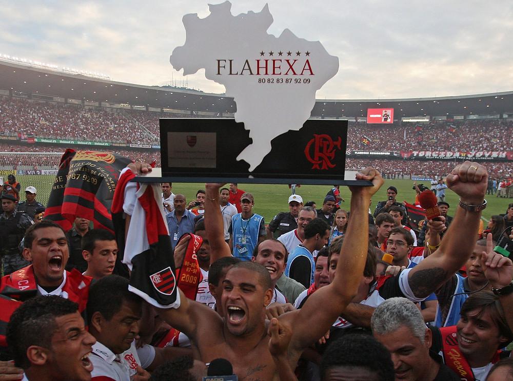 Adriano Imperador, um dos heróis da conquista do hexacampeonato do Flamengo, ergue a simbólica taça de campeão, rodeado de seus companheiros de equipe.