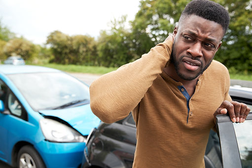 Male Motorist With Whiplash Injury In Car Crash Getting Out Of Vehicle.jpg