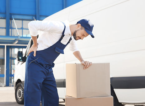 Delivery man suffering from pain after moving heavy box near car.jpg