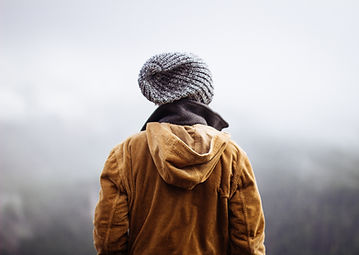 Image of a person in yellow jacket walking away and into fog