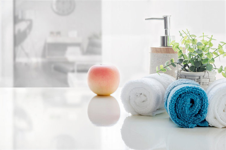 rolled-clean-towels-white-table-with-blu