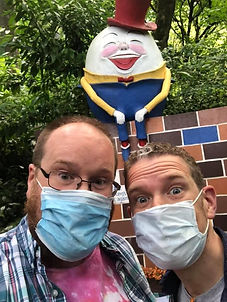 2 men wearing masks in front of humpty dumpty
