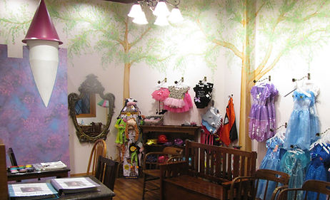 Facepainting store with tree mural and costumes on the wall