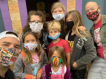 Family wearing masks in front of castle entrance