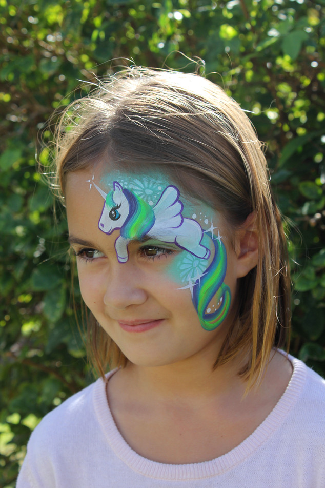 Cute winged unicorn face painting design with teal and purple hair.