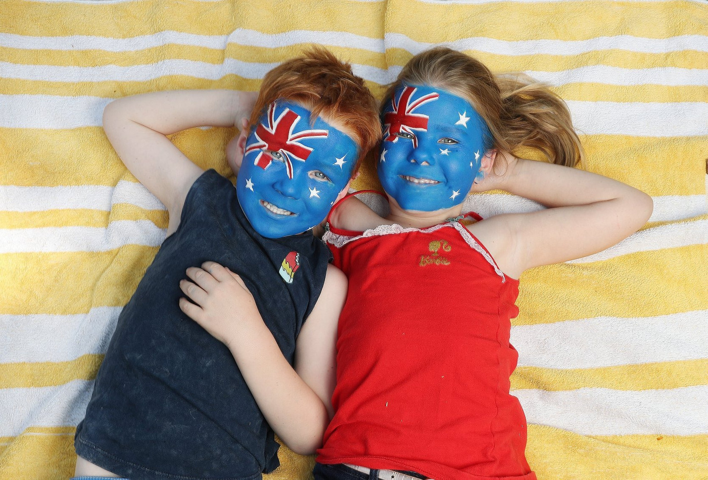 Siblings with Australian flag face paint designs, painted by Beth Joyce for the Brisbane Courier Mail.