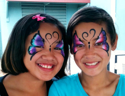 Two girls with matching colourful butterfly face painting designs by Beth Joyce.