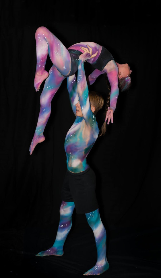 Two young acrobats painted with galaxy inspired swirls and washes of colour in shades of purple, blue and teal.
