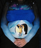 Belly painting depicting Emperor penguin parents and their chick in an icy landscape under the lights of Aurora Australis. Painted by Brisbane belly painter Beth Joyce.