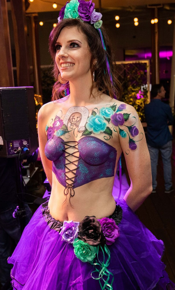 Daf of the Dead inspired corset painted in shades of purple, with painted purple and teal roses.