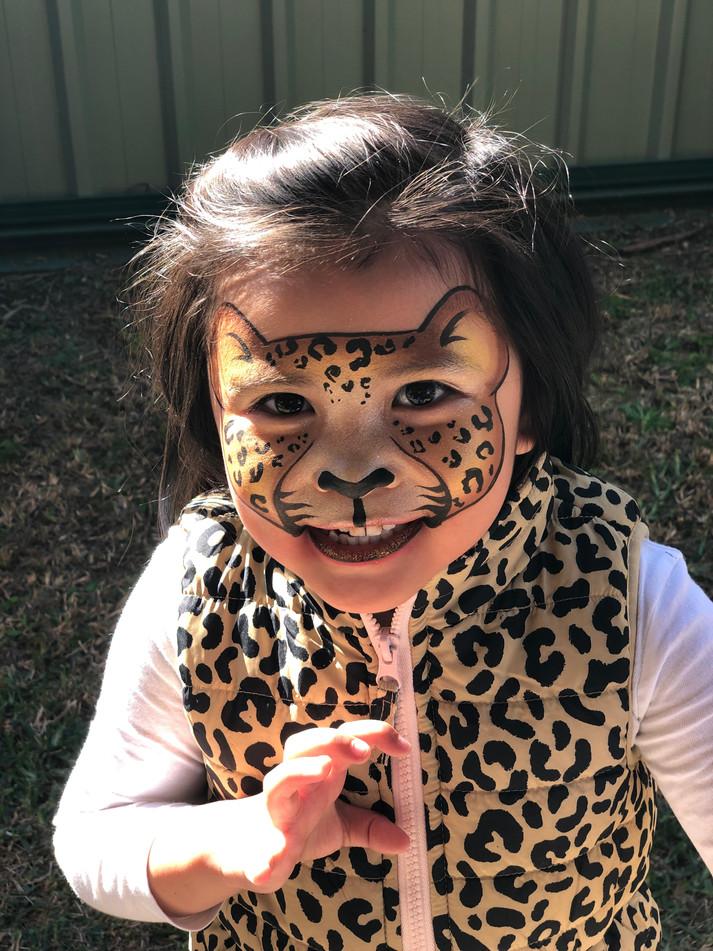 Cute leopard face paint design to match her leopard print vest