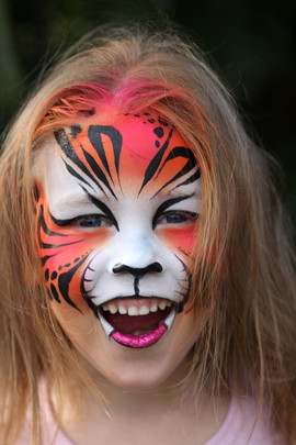 Brightly coloured orange and pink tiger face painting