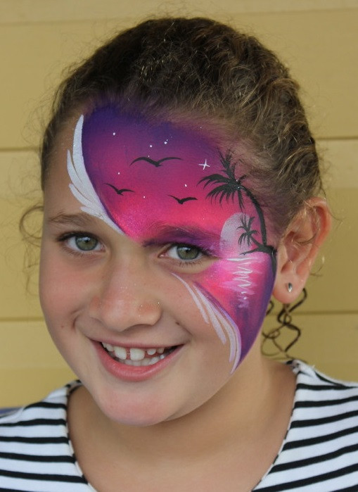 Beautiful face paint design of a full moon rising over a tropical beach.