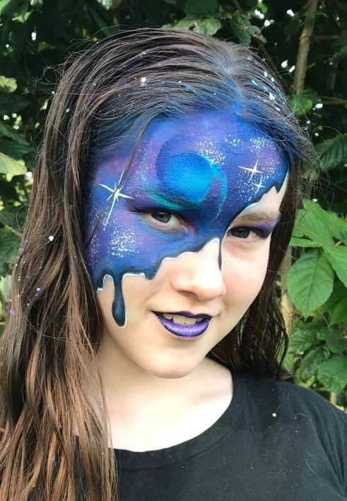 Galaxy face paint makeup in shades of blue and purple with sparkly stars.