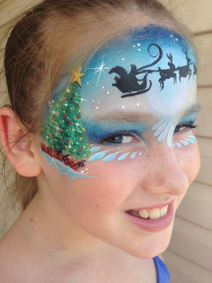 Christmas face painting design on the forehead with a Christmass tree and a silhouette of Santa and his sleigh.