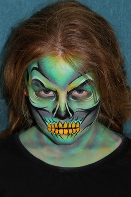 Scary teal monster face painting with horrible yellow teeth
