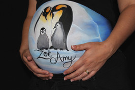 Stunning belly painting of a pair of Emperor Penguins with their baby on the ice under a dark sky painted by Brisbane body painter Beth Joyce