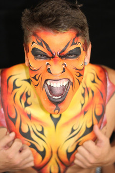 Flaming monster face paint design in shades of red, orange and yellow.