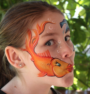 Fanciful goldfish design painted on the cheek using the childs mouth as the mouth of the fish.