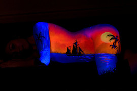UV neon glowing tropical sunset with a silhouette of a sailboat in the foreground painted by Brisbane body painter Beth Joyce