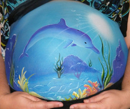 Under the sea belly painting design with a dolphin swimming through the gentle suns rays through the water, surrounded by seaweed and corals