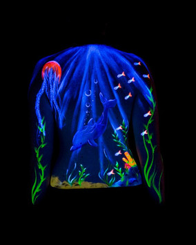 A glowing UV underwater scene including fish, a dolphin and jellyfish swimming among the seaweed.