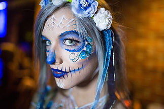 Day of the Dead inspired Sugar Skull in shades of blue, with rosebuds framing the eyes.