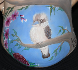 Beautiful belly painting of a young Kookaburra sitting in a gum tree with baby footprints and a name seeming to be carved into the trunk of the tree