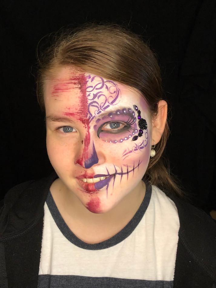 Elegant decorated skull face paint design in shades of purple.