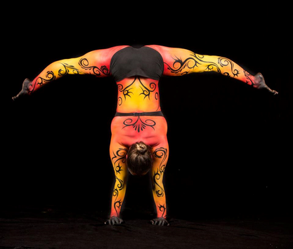 Stunning body painting in shades of red, orange and yellow with black tribal swirls painted on a female acrobat.