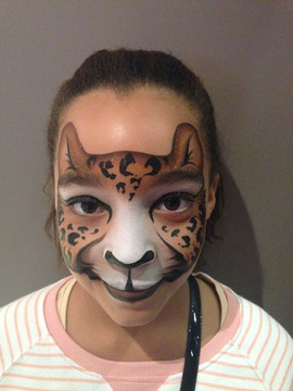 Beautiful young lady with a brown and gold leopard face painting design