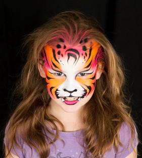 Neon coloured tiger face paint design by Brisbane artist Beth Joyce.