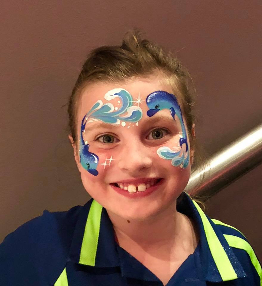 Two dolphins jump and swim through the waves in this face painting design by Beth Joyce.