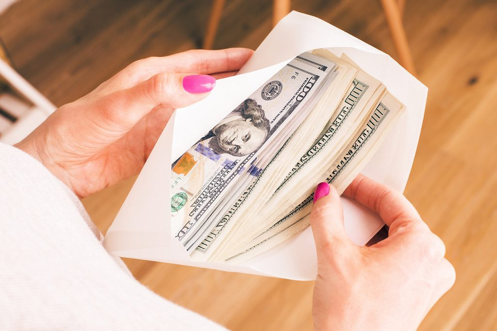 what is value investing? Woman holding cash envelope
